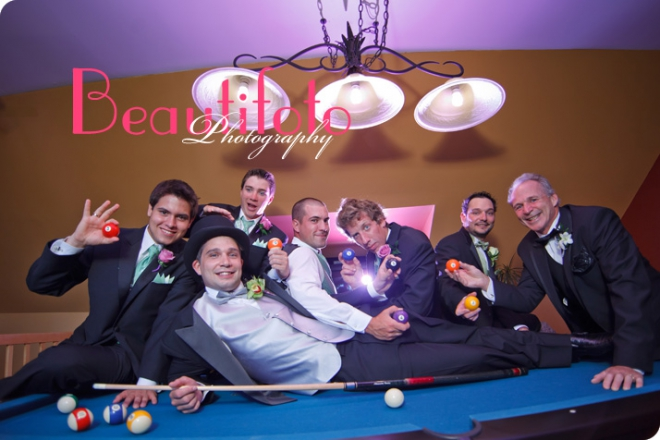 The groom lying on a pool table with the groom