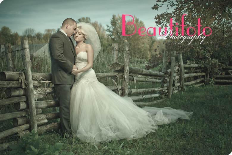 Bride and groom embrace by an old wooden fence.