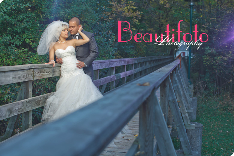 Bride and groom embrace on an old bridge. Photo by Beautifoto Montreal wedding photographer.
