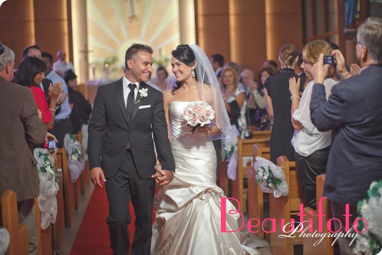 Bride and Groom walking down the isle at Maria Ausiliatrice church.